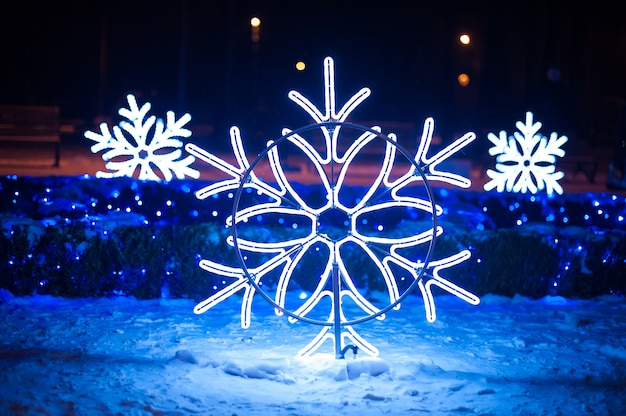 Iluminações de natal em forma de flocos de neve no parque noturno