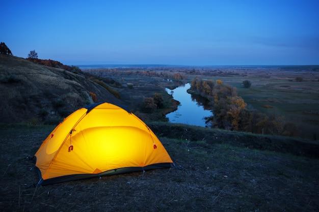 Iluminado dentro da tenda laranja em uma colina acima do rio