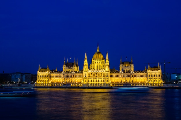 Iluminado o edifício do parlamento de budapeste à noite com céu escuro e reflexão no rio danúbio