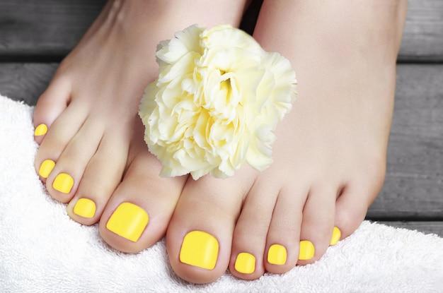 Iluminando pedicure amarela com flor em uma toalha