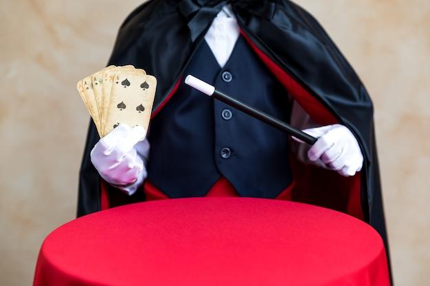 Ilusionista segurando varinha mágica e baralho.