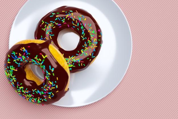 Ilustração 3d de dois donuts de chocolate com granulado multicolorido em um prato clássico branco isolado em um fundo rosa