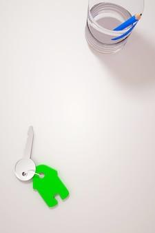 Ilustração 3d de uma chave de casa com um chaveiro verde na chave. chave com um chaveiro em uma mesa branca. lápis azul em um copo sobre uma mesa branca. gráficos 3d