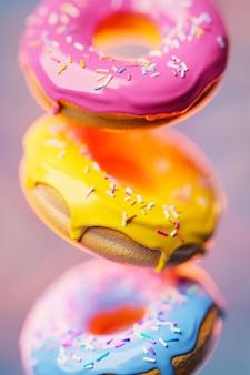 Ilustração 3d três donuts multicoloridos com granulado multicolorido voam