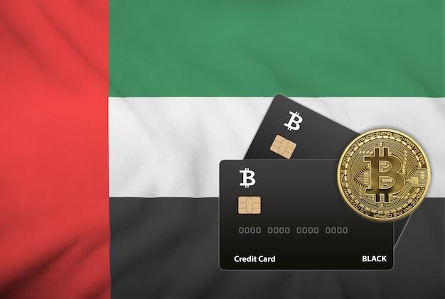 Ilustração de dois cartões de crédito pretos e moeda bitcoin no fundo da bandeira dos emirados árabes unidos