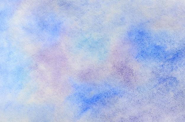 Ilustração de fundo abstrata sob a forma de pinceladas de aquarela e gotas, executadas em tons de azuis e roxos frios