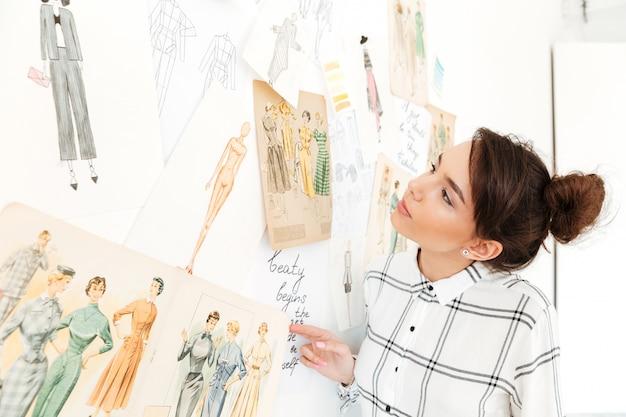 Ilustrador de moda feliz senhora em pé perto de muitas ilustrações