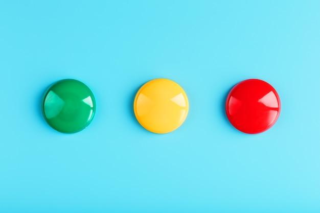 Ímã redondo verde amarelo e vermelho em uma linha em uma superfície azul na forma de um símbolo de semáforo