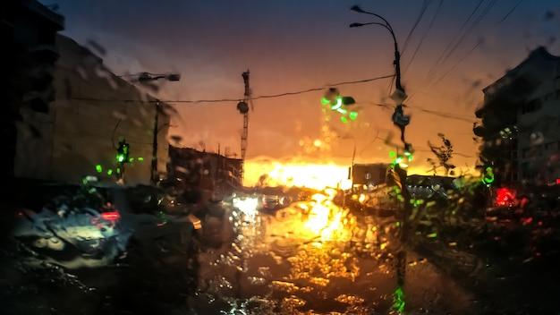 Imagem abstrata através do pára-brisa do carro molhado no transporte em movimento e automóveis na chuva ao pôr do sol