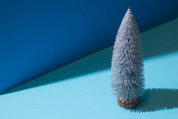 Imagem abstrata de uma árvore de natal decorativa em um fundo azul.
