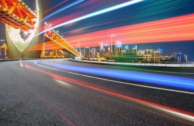 Imagem abstrata do movimento borrão de carros na estrada da cidade à noite, arquitetura urbana moderna em chongqing, china