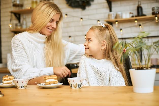 Imagem aconchegante de jovem mãe feliz com longos cabelos loiros posando na cozinha com sua adorável filha, sentada à mesa, tomando chá e comendo bolo, olhando uma para a outra, sorrindo, conversando