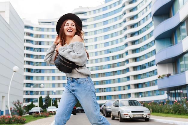 Imagem ao ar livre da menina alegre no chapéu de lã preto e blusa cinza cair pulando e apreciando o passeio na cidade urbana moderna.