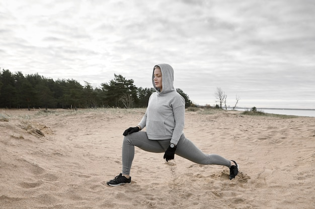 Imagem ao ar livre de atraente magro musculoso jovem atleta no sportswear moderno, exercitando-se na praia, fazendo investidas, aquecendo o corpo antes de correr. esportes, condicionamento físico, flexibilidade e força