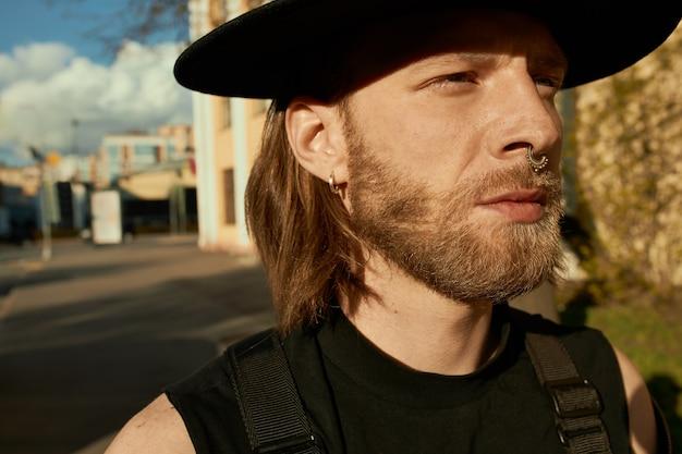 Imagem ao ar livre de um jovem bonito com a barba por fazer usando brincos, piercing no nariz e chapéu preto, caminhando na rua da cidade, aproveitando o dia de sol