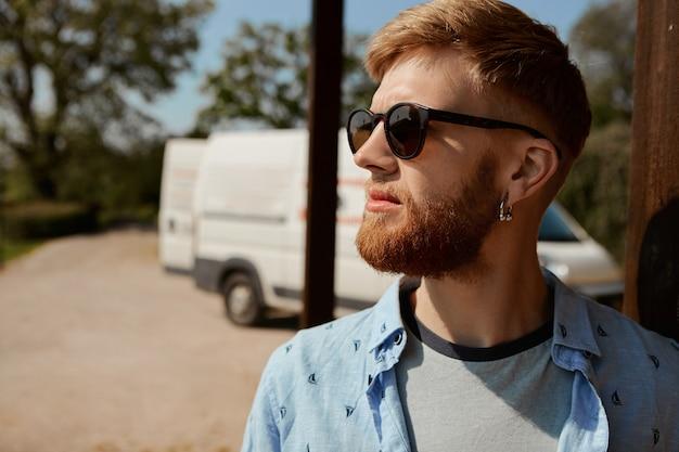 Imagem ao ar livre de um jovem caucasiano barbudo vestindo óculos escuros