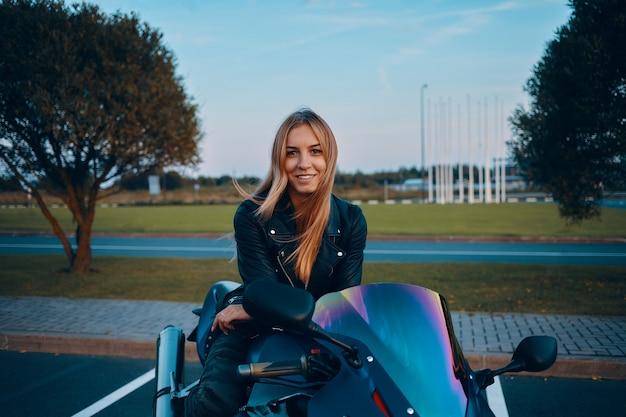Imagem ao ar livre de uma jovem europeia atraente com cabelo loiro solto, sentada em uma moto azul, vestida com jeans camuflados e jaqueta de couro preta
