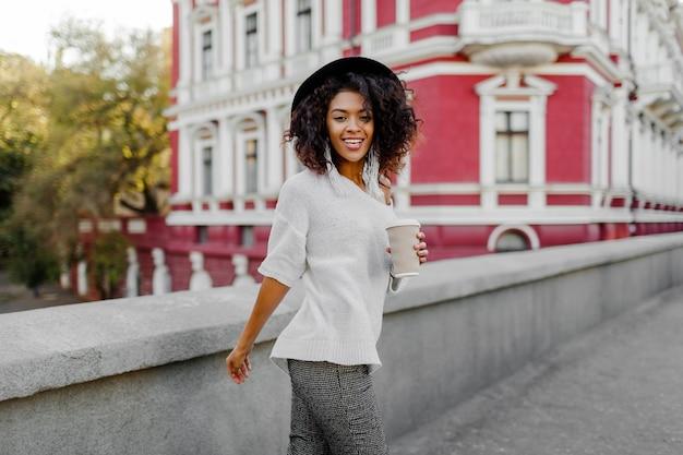 Imagem ao ar livre do estilo de vida de mulher negra feliz andando na cidade de primavera com uma xícara de cappuccino ou chá quente. roupa de hipster. camisola branca tamanho grande, chapéu preto, acessórios elegantes.