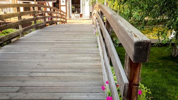 Imagem aproximada da bela e velha ponte de madeira sobre um pequeno rio calmo na velha cidade europeia