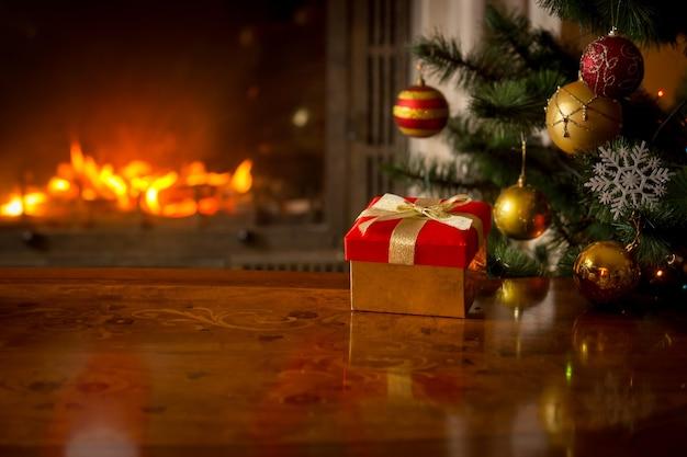 Imagem aproximada da caixa de presente vermelha na mesa de madeira em frente à lareira e à árvore de natal