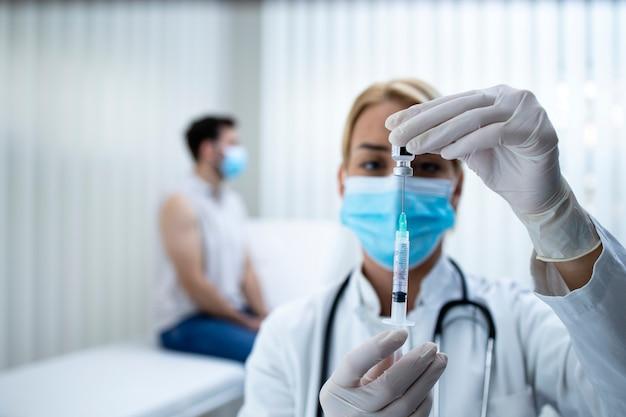 Imagem aproximada da enfermeira preparando a injeção da vacina para o paciente durante a epidemia do vírus corona