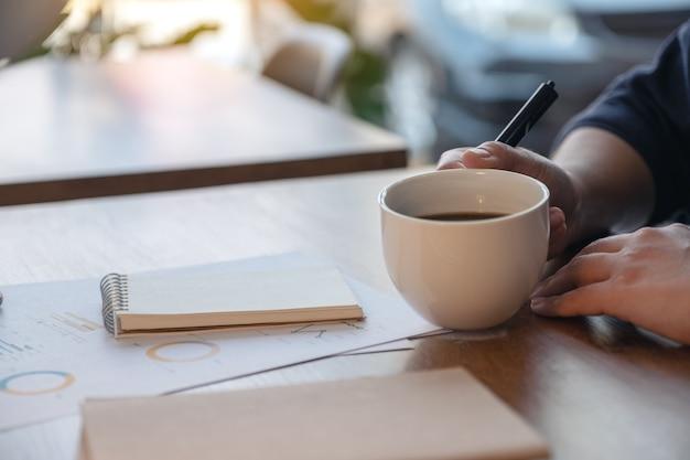 Imagem aproximada da mão de uma mulher segurando uma xícara de café quente enquanto trabalha em um documento de negócios na mesa de madeira