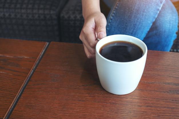 Imagem aproximada da mão de uma mulher segurando uma xícara de café quente para beber enquanto está sentada no café