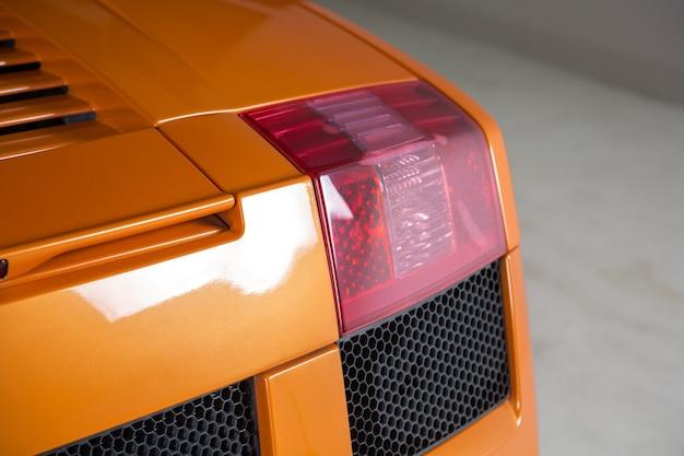 Imagem aproximada das luzes de fundo de um carro laranja moderno