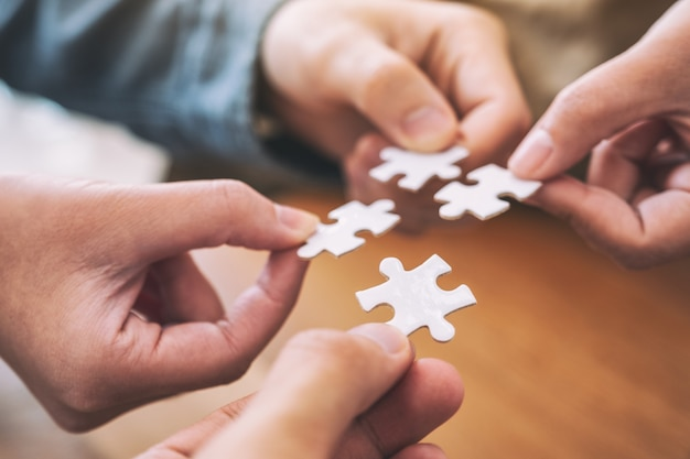 Imagem aproximada das mãos das pessoas segurando e montando uma peça do quebra-cabeça branco