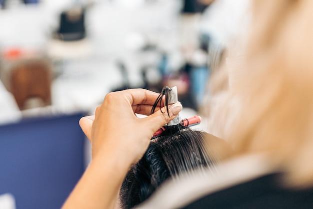 Imagem aproximada das mãos de um cabeleireiro usando um rolo para enrolar o cabelo de uma cliente