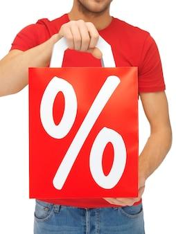 Imagem aproximada das mãos de um homem segurando uma sacola de compras