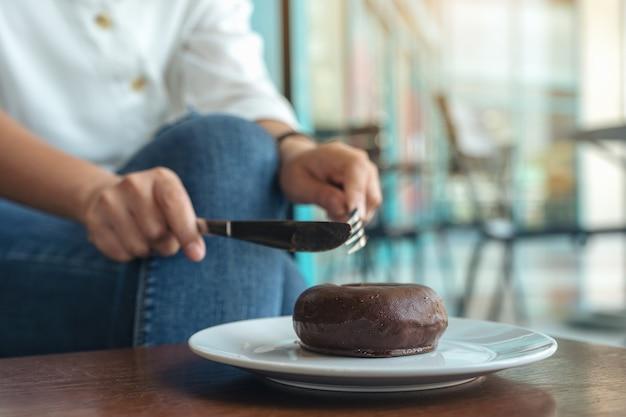 Imagem aproximada das mãos de uma mulher cortando um pedaço de donut de chocolate para comer com garfo e faca em um prato branco