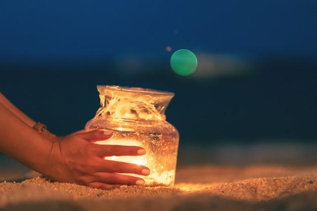 Imagem aproximada das mãos de uma mulher segurando e colocando uma garrafa de vidro em suportes para velas na praia à noite