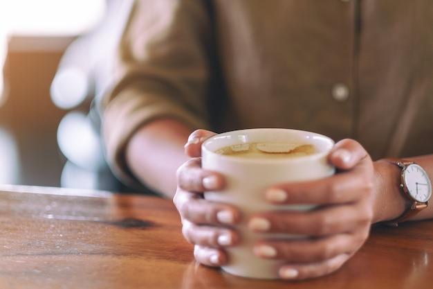 Imagem aproximada das mãos de uma mulher segurando uma xícara de café quente na mesa de madeira