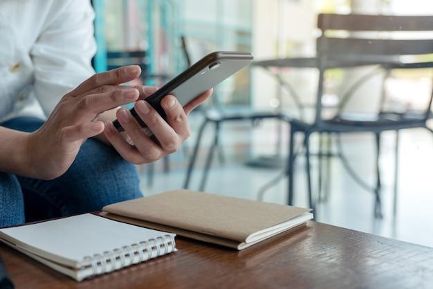 Imagem aproximada das mãos de uma mulher segurando, usando e enviando mensagem de texto de telefone inteligente em um café