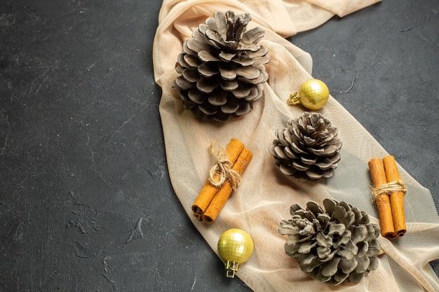 Imagem aproximada de acessórios de decoração de limão e três cones de coníferas em uma toalha de cor nude sobre fundo de cor preta