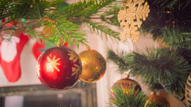 Imagem aproximada de bugigangas vermelhas e douradas penduradas na árvore de natal
