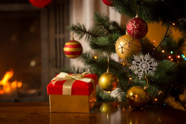 Imagem aproximada de caixa de presente de natal vermelha com fita dourada ao lado da árvore de natal decorada e lareira a lenha