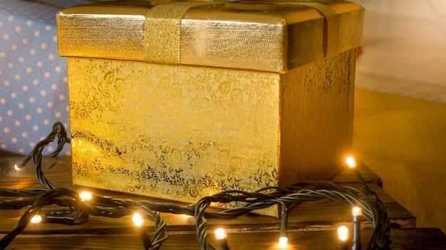 Imagem aproximada de caixa de presente dourada e luzes de natal brilhantes