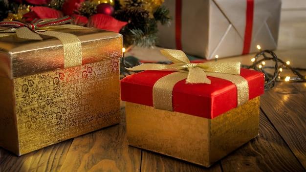 Imagem aproximada de caixas de presente de natal vermelhas e douradas no chão de madeira
