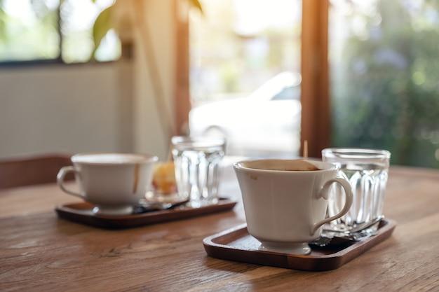 Imagem aproximada de canecas brancas de café quente e copos de água na mesa de madeira do café