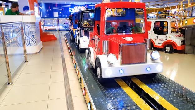 Imagem aproximada de carros elétricos coloridos no carrossel do parque de diversões em um shopping center