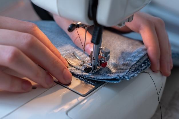 Imagem aproximada de costura em uma máquina de costura, mãos direcionando o tecido, foco de luz