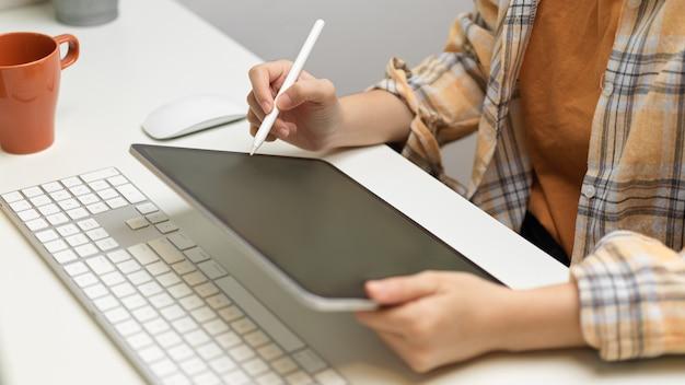 Imagem aproximada de designer gráfico feminino trabalhando com tablet digital na mesa branca