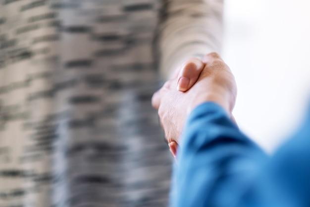 Imagem aproximada de duas pessoas apertando as mãos