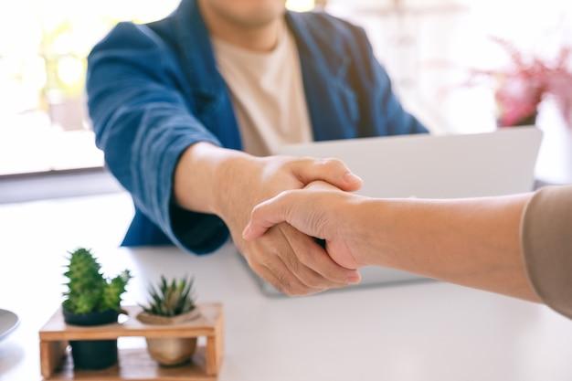 Imagem aproximada de empresários apertando as mãos no escritório