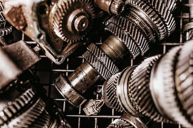 Imagem aproximada de engrenagens de metal sujas em uma grade sob luz