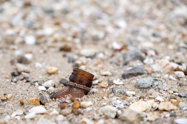 Imagem aproximada de garrafas de vidro quebradas na praia