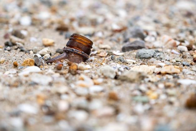 Imagem aproximada de garrafas quebradas na praia
