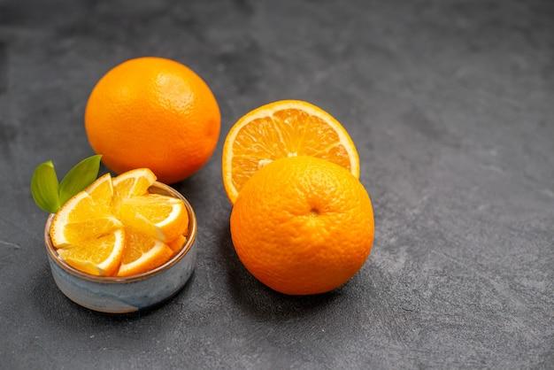 Imagem aproximada de laranjas frescas inteiras e picadas na mesa escura
